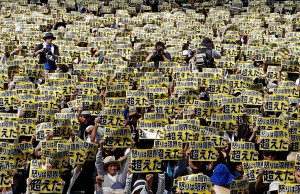 Protesters raise placards reading 'Anger was over the limit' during a rally against U.S. military bases in Naha