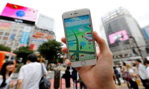 "A man poses with his mobile phone displaying the augmented reality mobile game ""Pokemon Go"" by Nintendo in front of a busy crossing in Shibuya district in Tokyo"