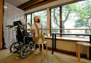 "A carer feeds a resident on a wheelchair at the private nursing home ""Silver Villa Koyama"" in Tokyo"