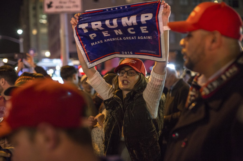 Donald Trump supporters rally outside of the Hilton Hotel in Midtown Manhattan.