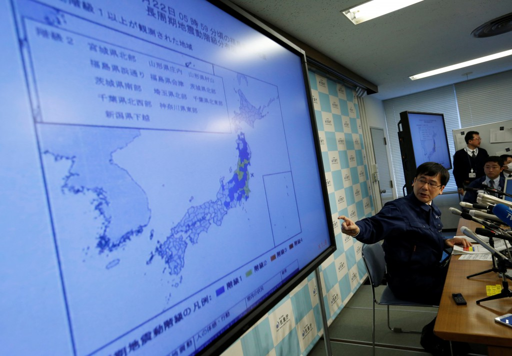 Japan Meteorological Agency's earthquake and volcano observations division director Koji Nakamura points at a map showing earthquake information during a news conference in Tokyo,