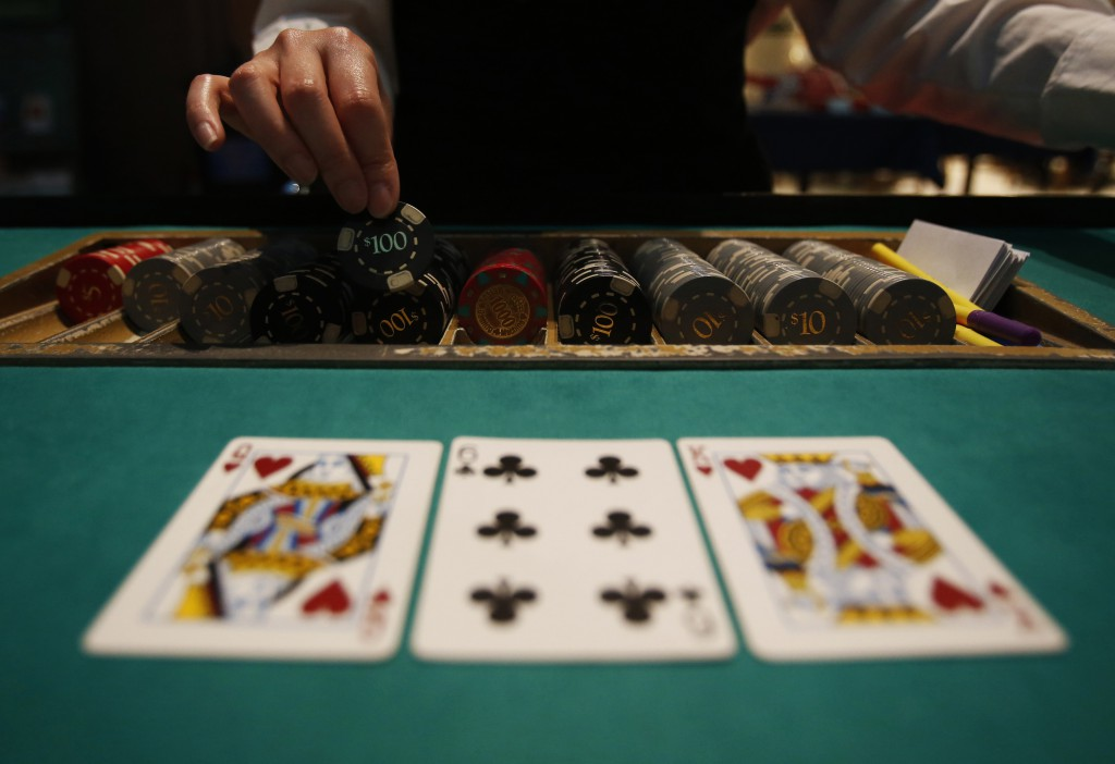 A dealer picks up chips on a mock black jack casino table during a photo opportunity at an international tourism promotion symposium in Tokyo