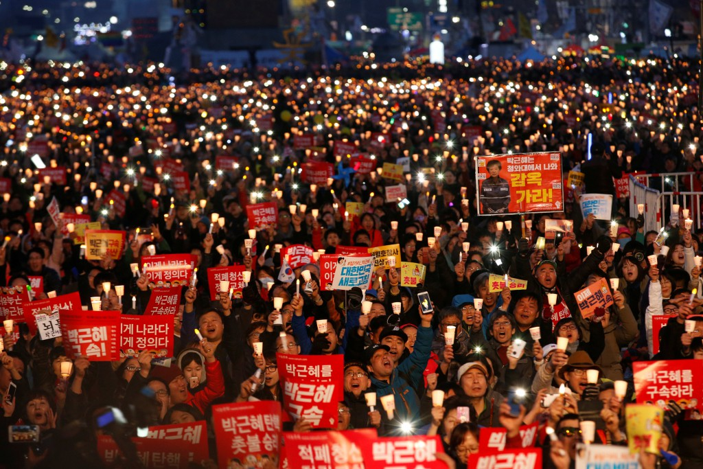 Protesters hold candles as they celebrate the impeachment of South Korea's ousted leader Park Geun-hye at a rally in Seoul